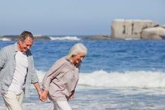 Pares mayores que recorren en la playa Imagenes de archivo