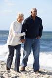 Pares mayores que recorren a lo largo de la playa junto Foto de archivo