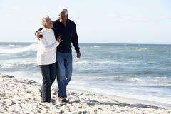 Pares mayores que recorren a lo largo de la playa junto Imágenes de archivo libres de regalías