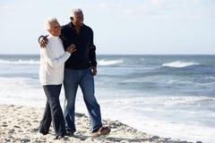 Pares mayores que recorren a lo largo de la playa junto Foto de archivo libre de regalías