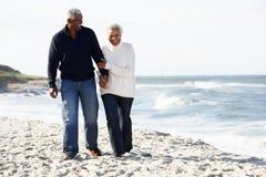 Pares mayores que recorren a lo largo de la playa junto Imagen de archivo libre de regalías