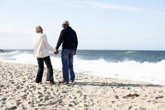 Pares mayores que recorren a lo largo de la playa junto Fotos de archivo
