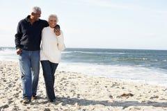 Pares mayores que recorren a lo largo de la playa junto fotos de archivo libres de regalías