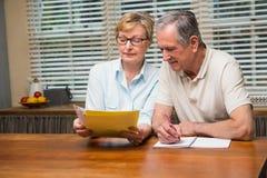 Pares mayores que resuelven sus cuentas Imágenes de archivo libres de regalías