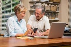 Pares mayores que resuelven sus cuentas Foto de archivo