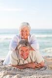 Pares mayores que se acuestan en la playa Imágenes de archivo libres de regalías