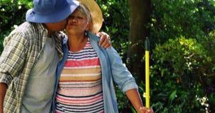 Pares mayores que se besan en jardín almacen de metraje de vídeo