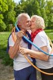 Pares mayores que se besan en un aro en naturaleza Foto de archivo