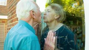 Pares mayores que se besan a través del vidrio metrajes
