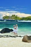 Pares mayores que se colocan en el abarcamiento de la playa Imágenes de archivo libres de regalías