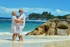 Pares mayores que se colocan en el abarcamiento de la playa Foto de archivo libre de regalías