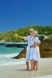 Pares mayores que se colocan en el abarcamiento de la playa Imagen de archivo libre de regalías