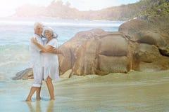 Pares mayores que se colocan en el abarcamiento de la playa Fotos de archivo