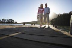 Pares mayores que se colocan en el embarcadero de madera que mira hacia fuera sobre el lago Imagenes de archivo
