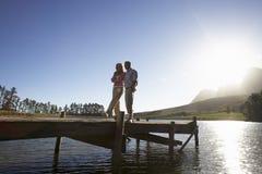 Pares mayores que se colocan en el embarcadero de madera que mira hacia fuera sobre el lago fotos de archivo