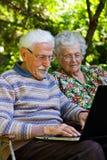 Pares mayores que se divierten con el ordenador portátil al aire libre Imágenes de archivo libres de regalías