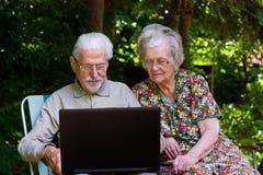 Pares mayores que se divierten con el ordenador portátil al aire libre Foto de archivo