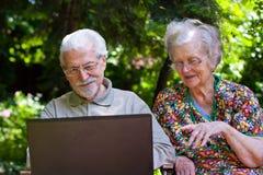 Pares mayores que se divierten con el ordenador portátil al aire libre Imagen de archivo