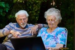 Pares mayores que se divierten con el ordenador portátil al aire libre Fotografía de archivo