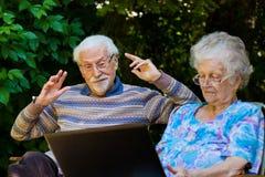Pares mayores que se divierten con el ordenador portátil al aire libre Imagenes de archivo