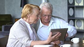 Pares mayores que se divierten en la comunicación con la familia en Internet en sala de estar cómoda almacen de video