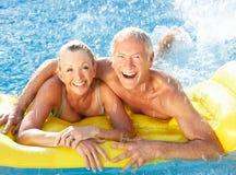 Pares mayores que se divierten en piscina Fotografía de archivo