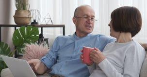 Pares mayores que se divierten usando el ordenador portátil en el sofá en casa metrajes