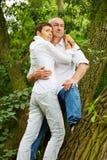 Pares mayores que se inclinan en árbol en bosque Imagenes de archivo