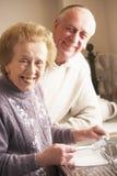 Pares mayores que se lavan para arriba en el fregadero Fotografía de archivo