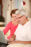 Pares mayores que se relajan en el país con la computadora portátil Foto de archivo libre de regalías