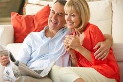 Pares mayores que se relajan en el sofá Fotos de archivo