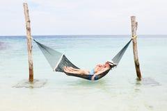 Pares mayores que se relajan en hamaca de la playa Foto de archivo