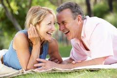 Pares mayores que se relajan en jardín del verano Imagen de archivo