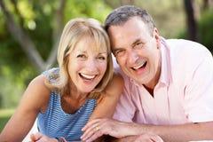 Pares mayores que se relajan en jardín del verano Fotografía de archivo