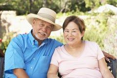 Pares mayores que se relajan en jardín junto Fotos de archivo