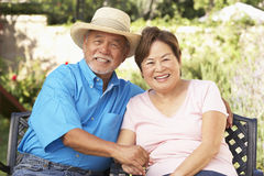 Pares mayores que se relajan en jardín junto Imagen de archivo libre de regalías