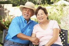 Pares mayores que se relajan en jardín junto Imágenes de archivo libres de regalías