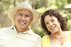 Pares mayores que se relajan en jardín junto Fotografía de archivo libre de regalías