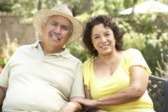 Pares mayores que se relajan en jardín junto Fotos de archivo libres de regalías