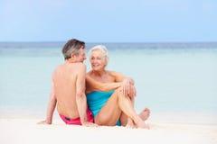 Pares mayores que se relajan en la playa hermosa junto Fotos de archivo