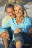 Pares mayores que se relajan en la playa junto por la tarde foto de archivo libre de regalías