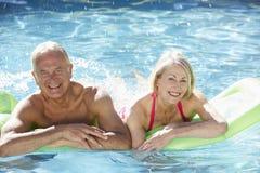 Pares mayores que se relajan en piscina en colchón neumático junto Foto de archivo libre de regalías