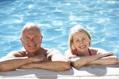 Pares mayores que se relajan en piscina junto Imagen de archivo
