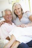 Pares mayores que se relajan en silla en casa Imagenes de archivo