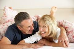 Pares mayores que se relajan junto en cama Imagen de archivo libre de regalías