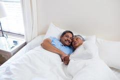 Pares mayores que se relajan junto en cama en dormitorio Fotos de archivo libres de regalías