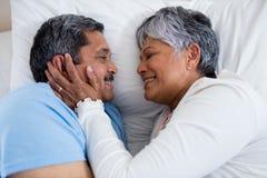 Pares mayores que se relajan junto en cama en dormitorio Foto de archivo libre de regalías