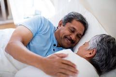 Pares mayores que se relajan junto en cama en dormitorio Fotografía de archivo