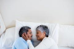 Pares mayores que se relajan junto en cama en dormitorio Fotografía de archivo libre de regalías