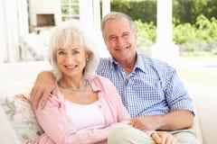 Pares mayores que se relajan junto en el sofá foto de archivo libre de regalías